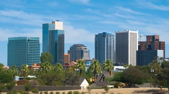 Downtown Phoenix skyline, with palm trees and a blue sky with clouds.